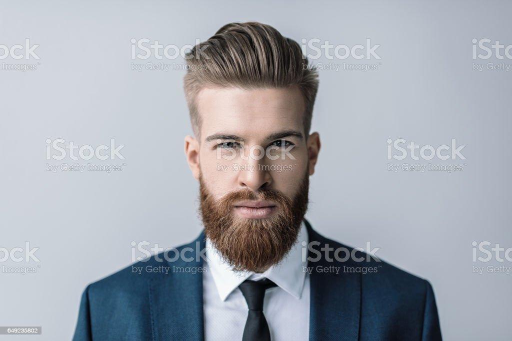 Elegante guapo barbudo hombre de negocios mirando a cámara - foto de stock