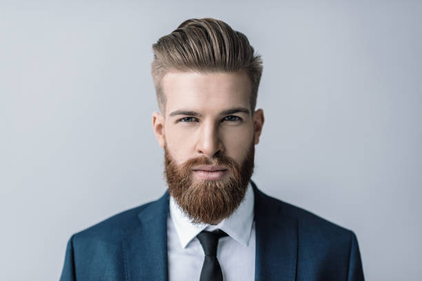 Stylish handsome bearded businessman looking at camera stock photo