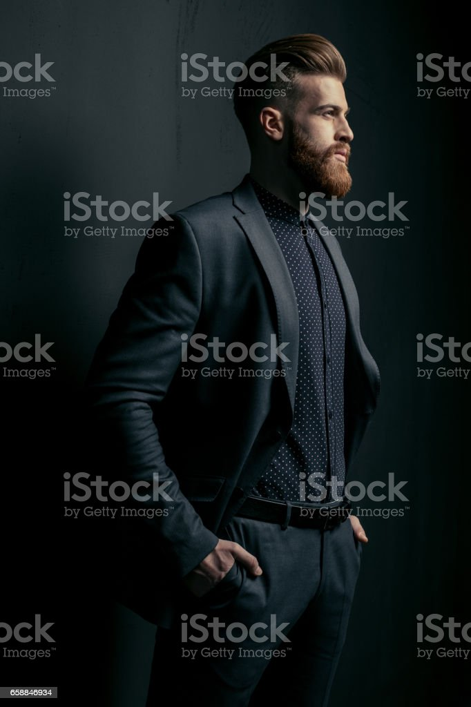 Stylish handsome bearded man in trendy suit looking away on black стоковое фото