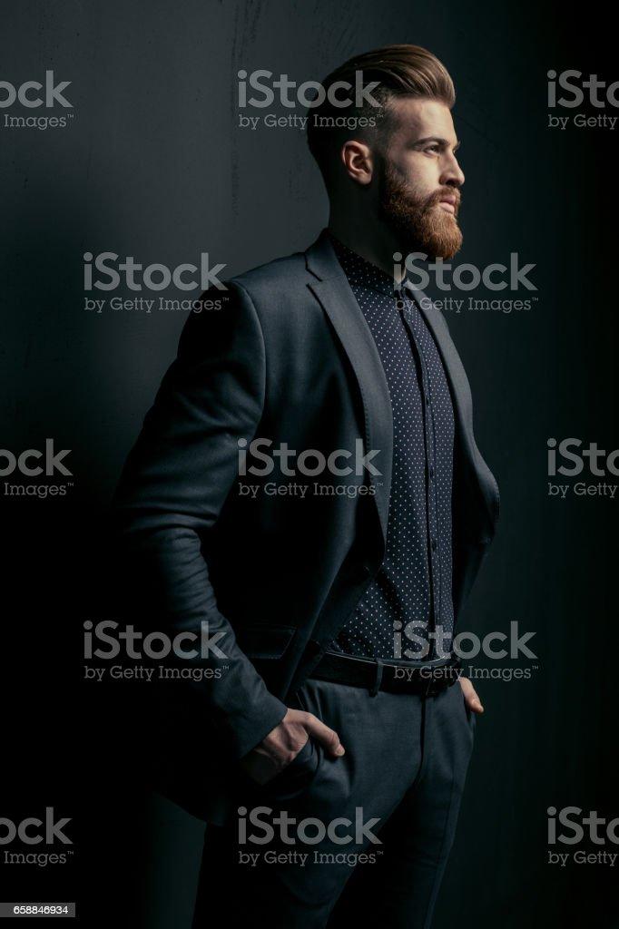 Elegante guapo hombre barbudo en traje de moda mirar lejos en negro - foto de stock