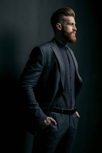 Stylish handsome bearded man in trendy suit looking away on black stock photo