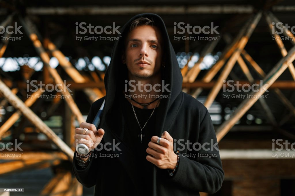 Stylish handsome man in a black robe with a hood holds a bat. stock photo