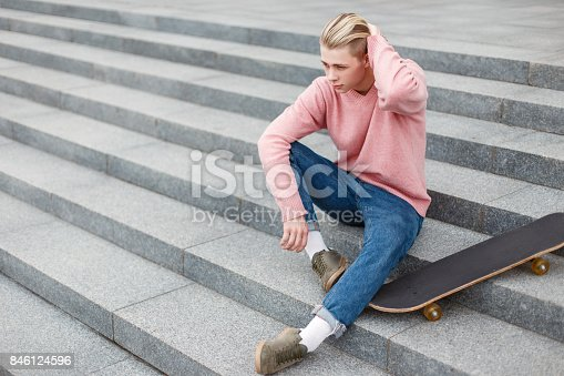 846124694 istock photo stylish handsome man in fashionable clothes with a skateboard sits on the steps 846124596