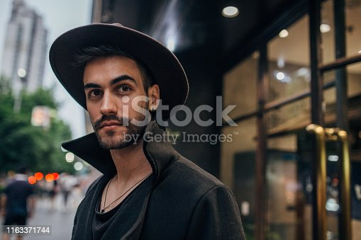 Handsome modern man with beard and hat, standing outdoors portrait.