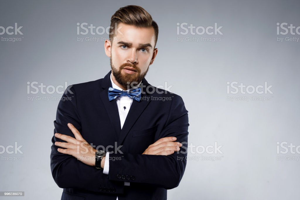 f3086eef7923 Stylish handsome man wearing a classic suit with bow-tie royalty-free stock  photo