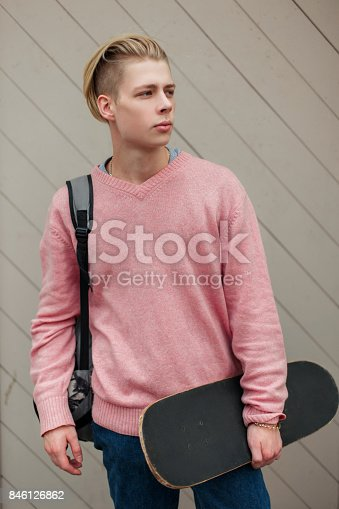 846124694 istock photo Stylish handsome man with a blonde hairstyle in a pink sweater with a backpack and a skateboard to the will of a wooden wall 846126862