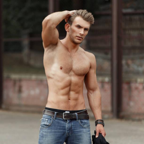 stilvolle hübscher junger mann mit einem schönen, gesunden körper mit muskeln auf der straße - sexsymbol stock-fotos und bilder