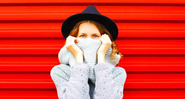 stilvolle glücklich herbst porträt frau verbirgt ihr gesicht halstuch auf rotem grund - mützenschal stock-fotos und bilder