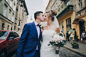 Stylish happy bride and groom walking and kissing in sunny city street. Gorgeous wedding couple of newlyweds embracing outdoors. Romantic moment