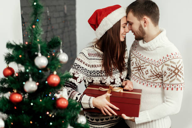 Stylish Happy Couple With Big Red Present Smiling Gently Hugging At Decorated Christmas Tree Joyful