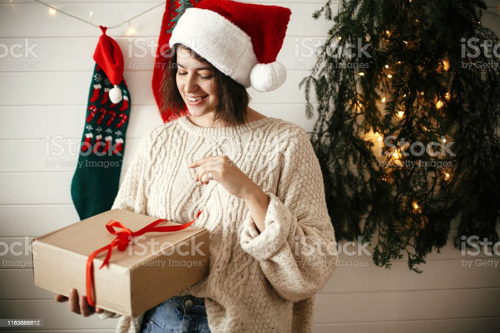 Stylish happy girl in festive sweater and santa hat opening gift box...