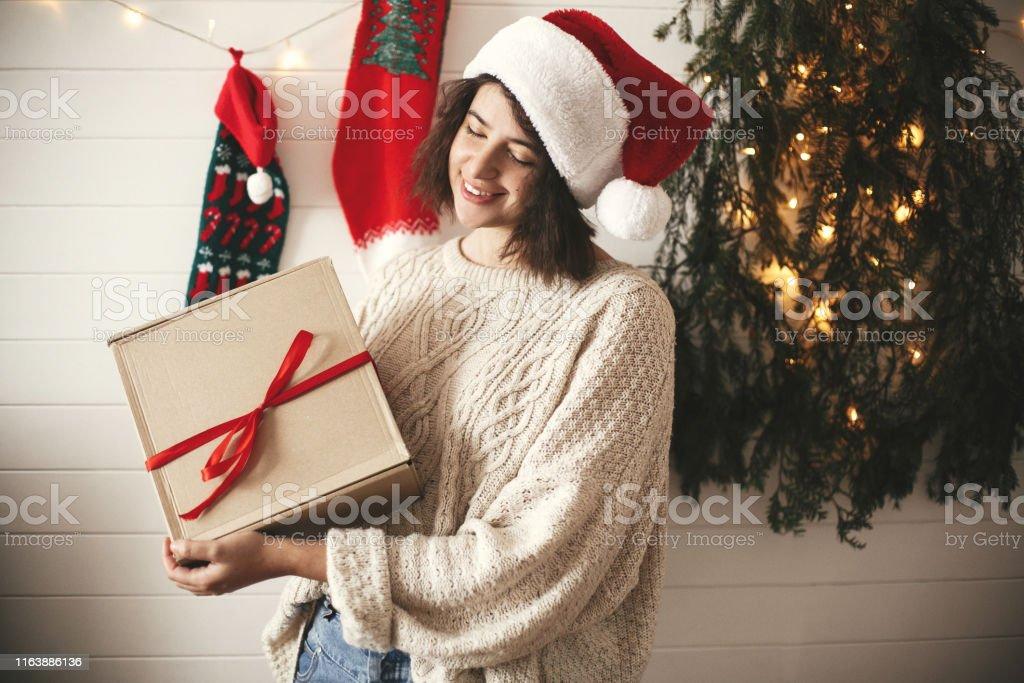 Stylish happy girl in santa hat holding christmas gift box on...