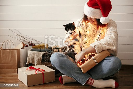 istock Stylish happy girl in santa hat smiling and playing with cute cat in festive christmas lights on background of modern presents. Young hipster woman in cozy sweater hugging kitty. Happy Holidays 1163892647