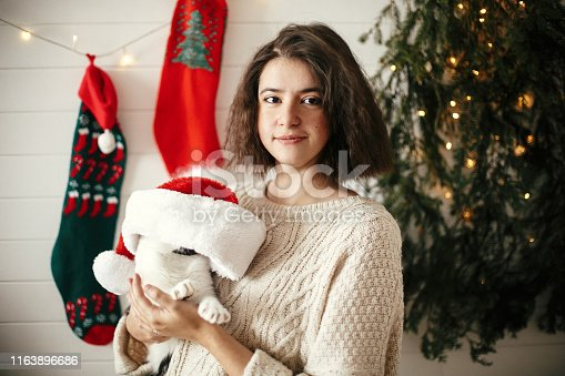 Stylish happy girl  playing with cute cat in santa hat in background of  christmas tree lights and stockings. Young hipster woman in cozy sweater hugging kitty. Happy Holidays