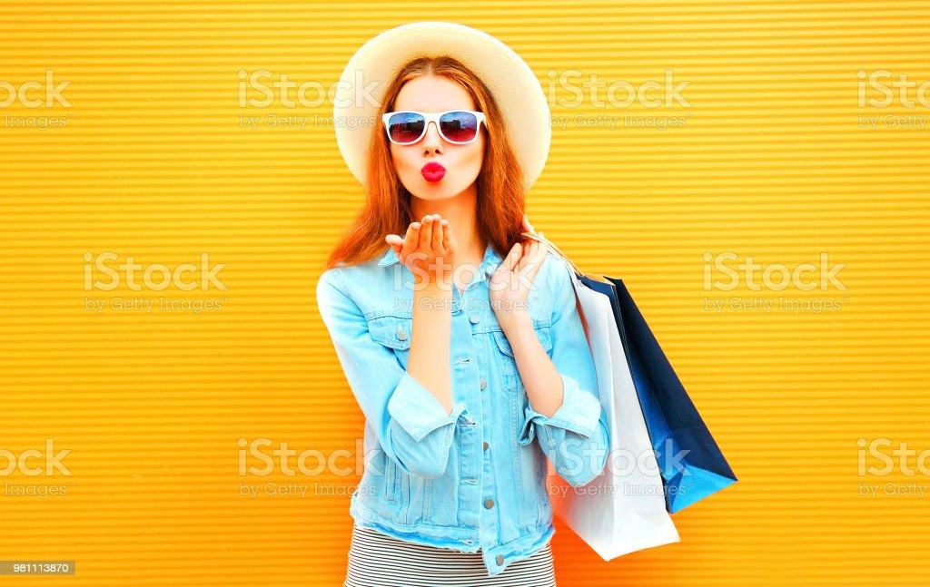 Fille heureuse élégante envoie qu un baiser d air est titulaire de des sacs 04cc639883ff