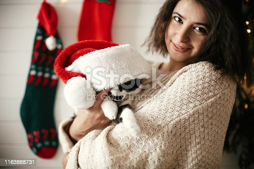 Stylish happy girl smiling and playing with cute cat in santa hat in background of  christmas tree lights and stockings. Young hipster woman in cozy sweater hugging kitty. Happy Holidays