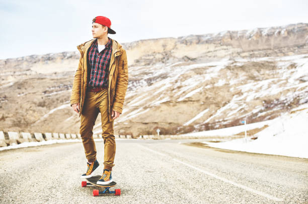 Stylish happy Young guy in a cap and trousers joggers rolling down a mountain road on a longboard, enjoying life stock photo