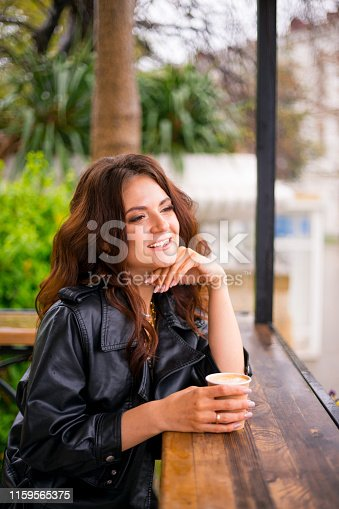870648602 istock photo Stylish happy young woman in street cafe. She holds coffee to go. 1159565375