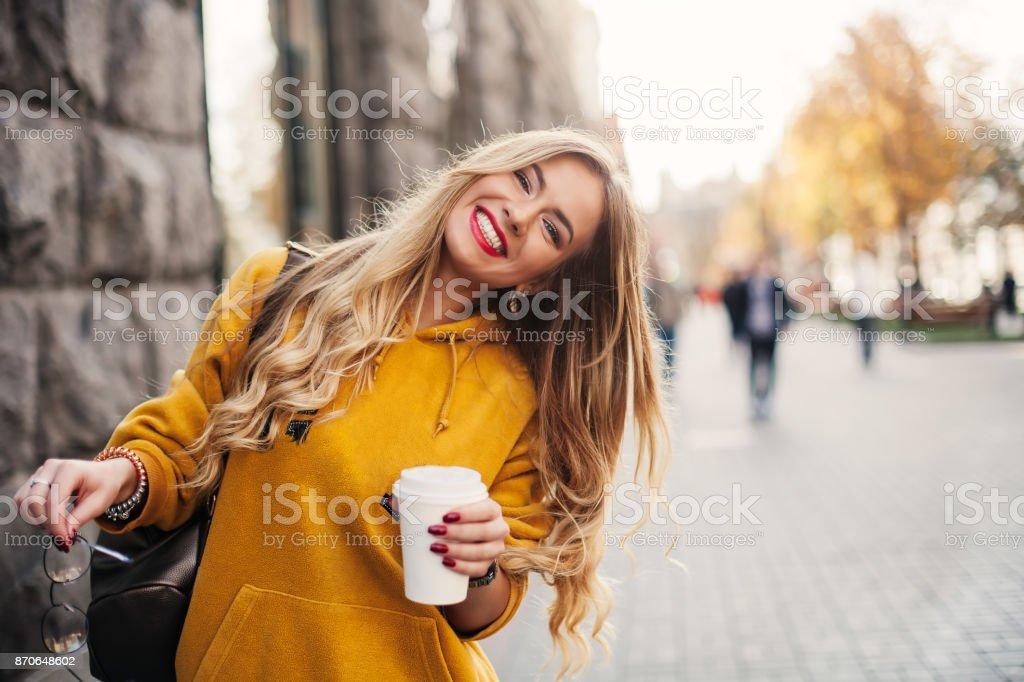 Stilvolle glückliche junge Frau trägt Boyfrend Jeans, weiße Turnschuhe helle gelbe Sweetshot. Sie hält Kaffee zum mitnehmen. Porträt von lächelndes Mädchen mit Sonnenbrille und mit Tasche Lizenzfreies stock-foto