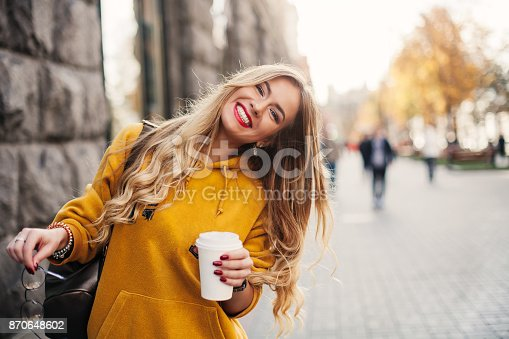 istock Stylish happy young woman wearing boyfrend jeans, white sneakers bright yellow sweetshot.She holds coffee to go. portrait of smiling girl in sunglasses and with bag 870648602