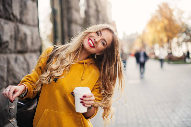 Stylish happy young woman wearing boyfrend jeans, white sneakers bright yellow sweetshot.She holds coffee to go. portrait of smiling girl in sunglasses and with bag stock photo