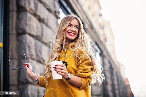 870648602 istock photo Stylish happy young woman wearing boyfrend jeans, white sneakers bright yellow sweetshot.She holds coffee to go. portrait of smiling girl in sunglasses and with bag 870648676