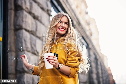 870648602 istock photo Stylish happy young woman wearing boyfrend jeans, white sneakers bright yellow sweetshot.She holds coffee to go. portrait of smiling girl in sunglasses and with bag 888124064