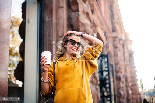 870648602 istock photo Stylish happy young woman wearing boyfrend jeans, white sneakers bright yellow sweetshot.She holds coffee to go. portrait of smiling girl in sunglasses and with bag 905771148