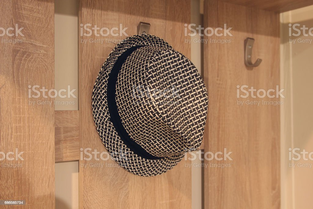 Stylish hat hanging on a hanger in the hallway Lizenzfreies stock-foto