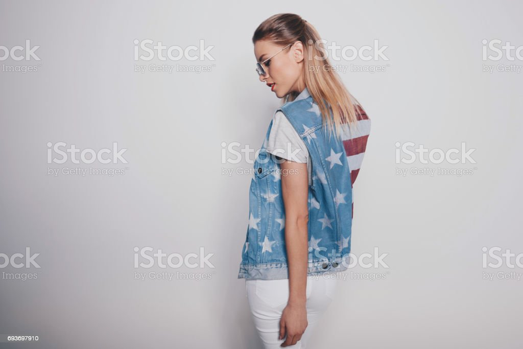 Stylish hipster blonde girl in american patriotic outfit and sunglasses stock photo