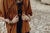 スタイリッシュな流行に敏感な自由奔放に生きる旅人女見てください。羽ブロンズ アクセサリー付きフリンジ ジャケットでジプシーの少女。ワンダー ラストの夏の旅行。大気の瞬間。テキ�
