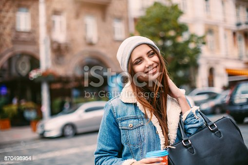 870648602istockphoto Stylish hipster girl in the retro jeans suit and knitted hat posing in the street She holds coffee to go, smiling friendly 870498954