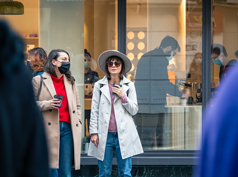 Bucharest, Romania - 03.13.2021: Stylish hipster girl wearing a hat and sun glasses holding a coffee cup in front of a coffee shop