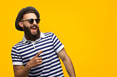 Stylish hipster man pointing away