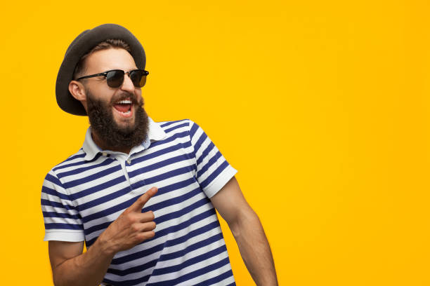stylish hipster man pointing away - hipster persona foto e immagini stock