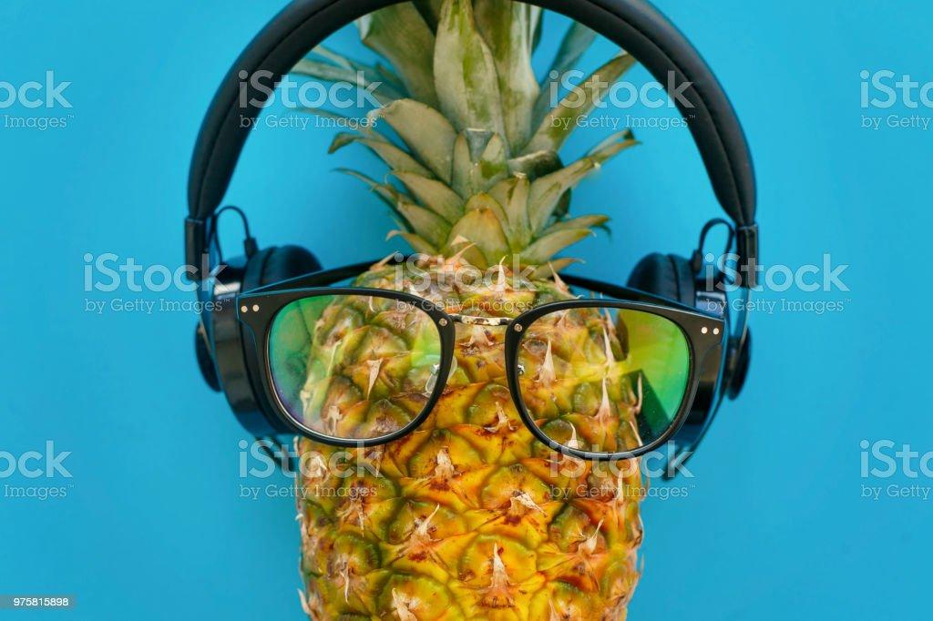 stilvolle Hipster Ananas in Gläsern und Kopfhörer auf trendiges blaues Papierhintergrund. Sommer flach zu legen. Urlaub und Party-Konzept. Platz für Text. Reisen und Urlaub - Lizenzfrei Ananas Stock-Foto