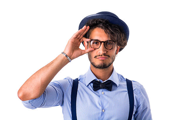 Stylish hipster with glasses, hat and bow-tie Portrait of brunette young man in glasses, hat, bow-tie, suspenders and shirt looking at camera. Studio shot, isolated on white suspenders stock pictures, royalty-free photos & images