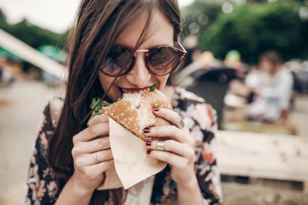 stilvolle hipster frau saftige burger essen. boho mädchen beißen leckeren cheeseburger, lächelnd street food festival. im sommer. sommer-urlaub-reisen-picknick. platz für text - partysalate stock-fotos und bilder