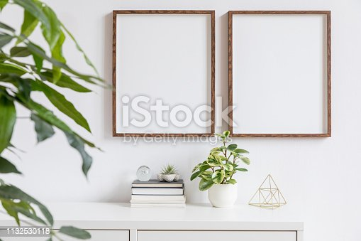 Minimalistic home decor of interior with mock up frames. Modern concept of white room with plants.