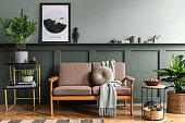 istock Stylish interior design of living room at cozy apartment with stylish sofa, plants, design furnitures, decoration and elegant accessories. Mock up poster frames on the shelf. Home staging. 1221631489