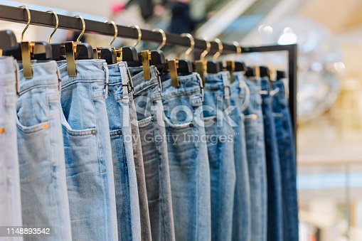 stylish jeans pants in a clothing store on the stands showcase with labels for the inscription
