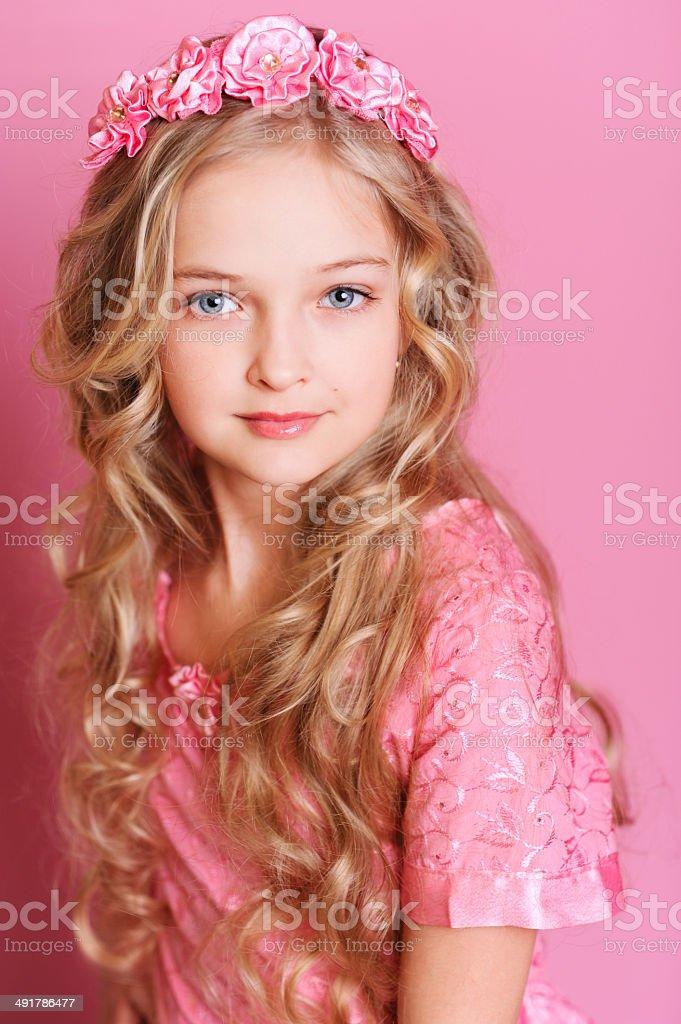 Stylish kid girl posing over pink stock photo