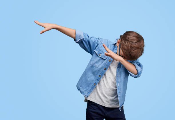 Stylish kid performing dab dancing stock photo