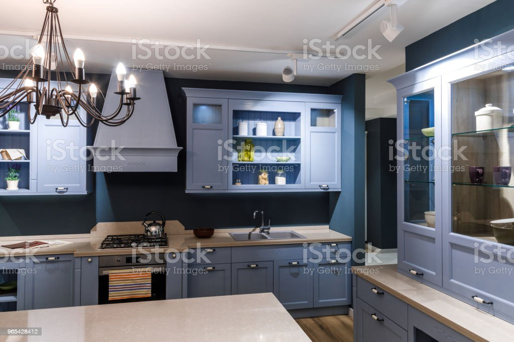 Stylish kitchen in blue tones with elegant chandelier royalty-free stock photo