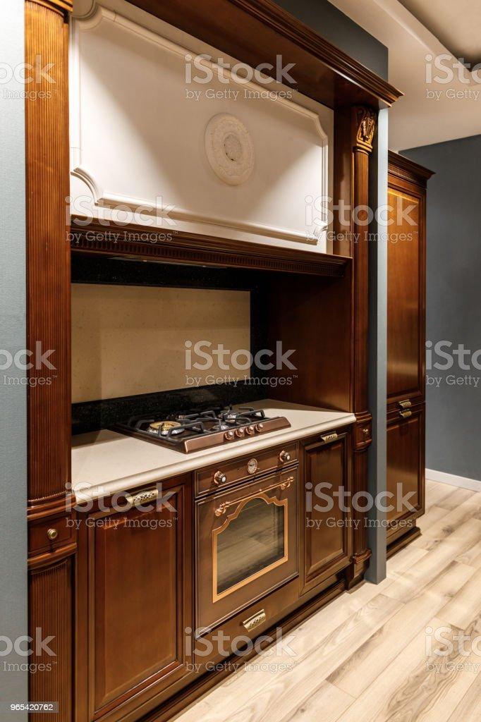Cuisine élégante avec comptoir en bois élégant et poêle - Photo de Ameublement libre de droits