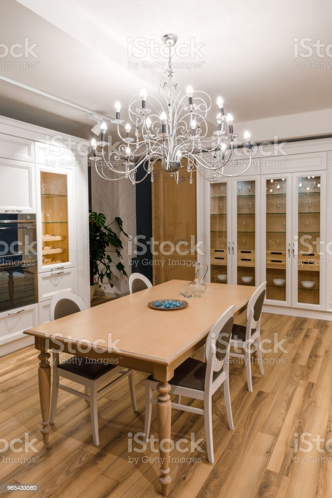 Stylish kitchen with elegant wooden table and chandelier royalty-free stock photo