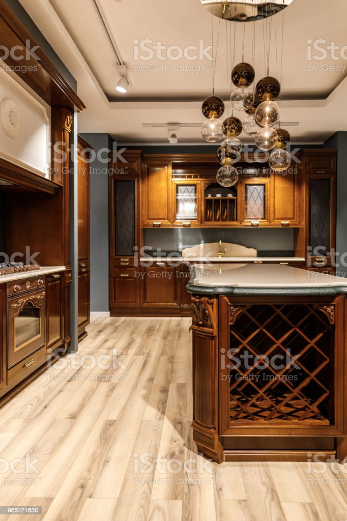 Stylish kitchen with large wooden counter and chandelier zbiór zdjęć royalty-free
