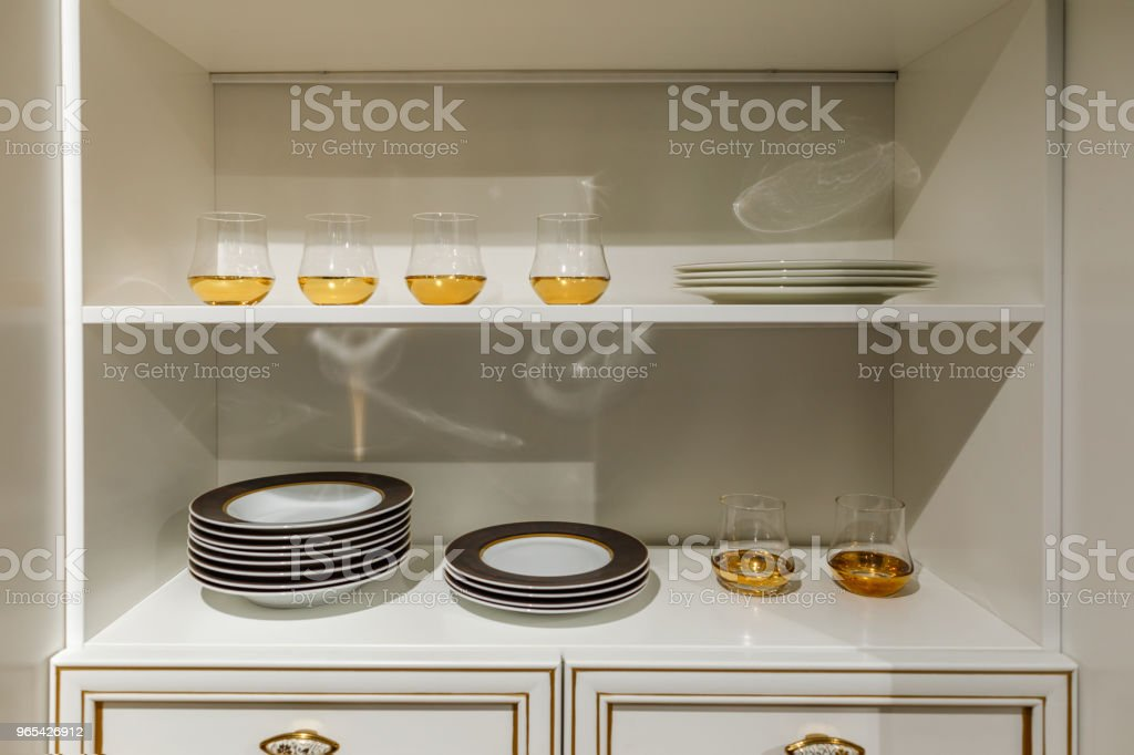 Stylish kitchen with modern tableware in cupboard zbiór zdjęć royalty-free