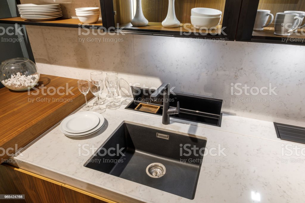 Stylish kitchen with tableware and sink on elegant wooden counter zbiór zdjęć royalty-free
