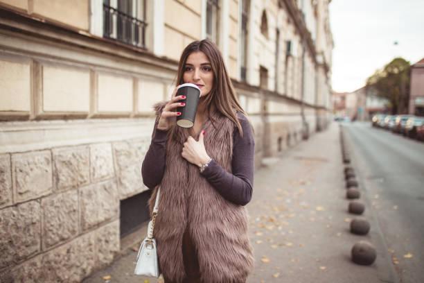stilvolle dame trinkt kaffee auf der straße - wintermantel damen wolle stock-fotos und bilder